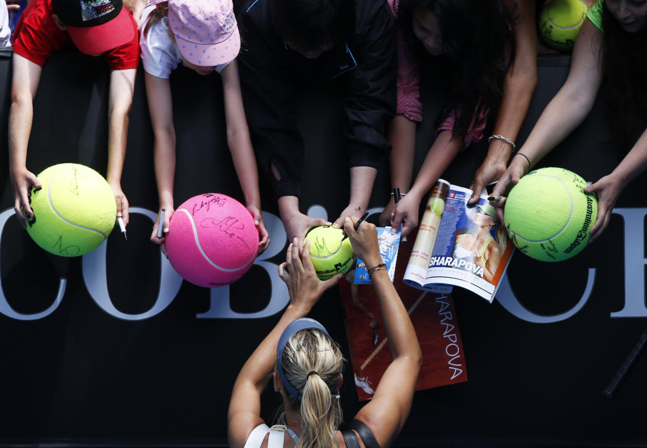Maria Sharapova of Russia signs autographs after defeating compatriot Olga Puchkova in their women's singles match at the Australian Open tennis tournament in Melbourne, January 14, 2013.    REUTERS/David Gray (AUSTRALIA  - Tags: SPORT TENNIS TPX IMAGES OF THE DAY)