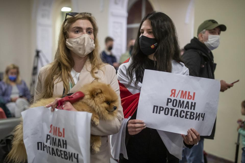 """Women one of them wearing an old Belarusian national flag hold posters reading """"I'm/we're Raman Pratasevich"""" as they wait to see passengers of the Ryanair plane with registration number SP-RSM, carrying opposition figure Raman Pratasevich which was traveling from Athens to Vilnius and was diverted to Minsk after a bomb threat, at the International Airport outside Vilnius, Lithuania, Sunday, May 23, 2021. The presidential press service said President Alexander Lukashenko personally ordered that a MiG-29 fighter jet accompany the Ryanair plane carrying opposition figure Raman Pratasevich and traveling from Athens, Greece, to Vilnius, Lithuania to the airport in the capital Minsk. (AP Photo/Mindaugas Kulbis)"""