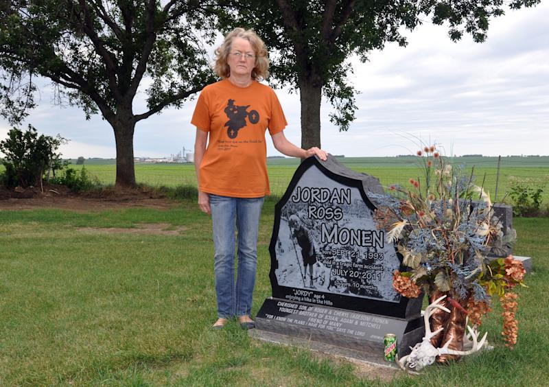 Cheryl Monen stands aside a gravestone for her youngest son, Jordan, who was killed last year in a farm accident, Wednesday, June 20, 2012, in Lester, Iowa. (AP Photo/Dirk Lammers)