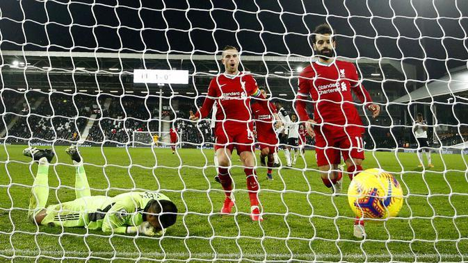 Pemain Liverpool Mohamed Salah (kanan) berlari untuk mengambil bola usai mencetak gol dari titik penalti ke gawang Fulham pada pertandingan Liga Premier Inggris di Stadion Craven Cottage, London, Minggu (13/12/2020). Liverpool dan Fulham bermain imbang 1-1. (AP photo/Matt Dunham, Pool)