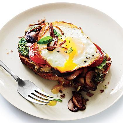 """<p>Top slices of multigrain bread with pesto, grated Parmigiano-Reggiano cheese, thick beefsteak tomato slices, plenty of sauteed mushrooms and shallots, fresh basil, and a fried egg for a flavorful and hearty open-faced <a href=""""https://www.myrecipes.com/course/breakfast-and-brunch-recipes/breakfast-sandwich-recipes"""" rel=""""nofollow noopener"""" target=""""_blank"""" data-ylk=""""slk:breakfast sandwich"""" class=""""link rapid-noclick-resp"""">breakfast sandwich</a>. </p>"""