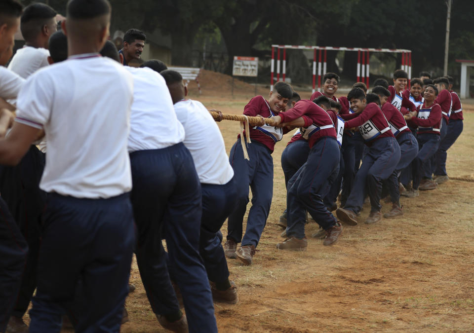 FILE - In this March 31, 2021, file photo, Indian army women recruits, right, compete with men in a tug-of-war as part of their training before they are inducted as the first women soldiers below officer rank, during a media visit in Bengaluru, India. India's top court on Wednesday, Sept. 22 allowed young women to take the entrance examination to the country's national defense academy for the first time in November, a watershed moment for them to join the armed forces as officers. The court had rejected the government plea that women were not suitable for commanding posts in the army, saying male troops were not prepared yet to accept female officers. (AP Photo/Aijaz Rahi)