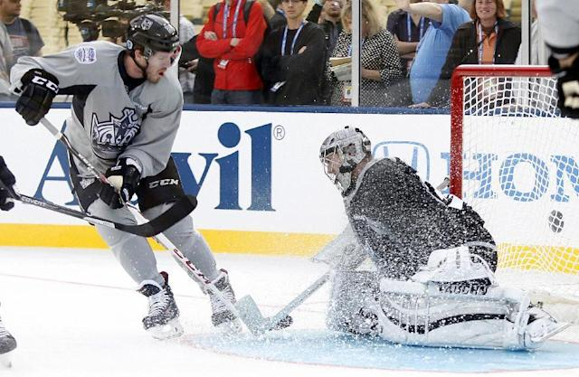 Los Angeles Kings center Colin Fraser, left, gives goalie Jonathan Quick, right, a snow wash during practice for the NHL Stadium Series hockey game Friday, Jan. 24, 2014, in Los Angeles. The Los Angeles Kings and Anaheim Ducks will play outdoors at Dodger Stadium on Saturday. (AP Photo/Alex Gallardo)