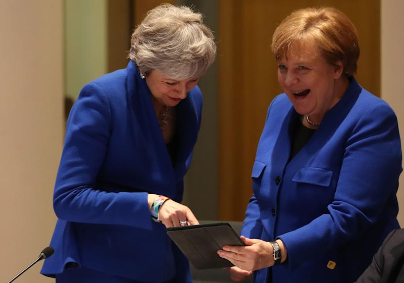 Britain's Prime minister Theresa May, left, and Germany's Chancellor Angela Merkel look at a tablet ahead of a European Council meeting on Brexit in Brussels on April 10, 2019.