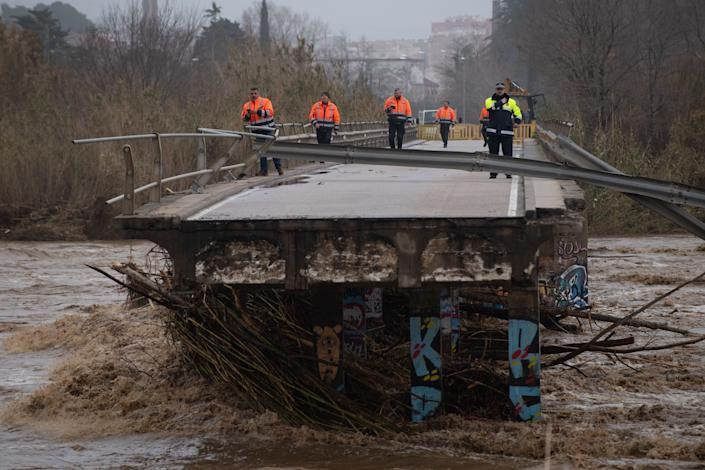 Policemen and security members walk on a fallen bridge in Malgrat de Mar, near Girona on January 22, 2020, as storm Gloria batters Spanish eastern coast. - - A winter storm which has killed three people lashed much of eastern Spain for a third day yesterday, cutting power, forcing the closure of schools and severing road and rail links. National weather agency Aemet placed most of northeastern Spain on alert because of the storm packing gusts of over 100 kilometres (60 miles) per hour, heavy snowfall, freezing rain and massive waves which smashed into seafront promenades, damaging shops and restaurants. (Photo by Josep LAGO / AFP) (Photo by JOSEP LAGO/AFP via Getty Images)