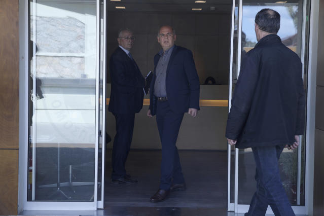 President of the Hellenic Football Federation Vagelis Grammenos , center, looks on at at the Hellenic Football Federation premises in Athens, on Wednesday, March 14, 2018. FIFA has sent a delegation to Greece to discuss the country's soccer crisis, after the government indefinitely suspended top league matches. The suspension followed a pitch invasion by the gun-toting owner of PAOK Thessaloniki Sunday after a late goal for his team was disallowed by the referee. (AP Photo/Petros Giannakouris)