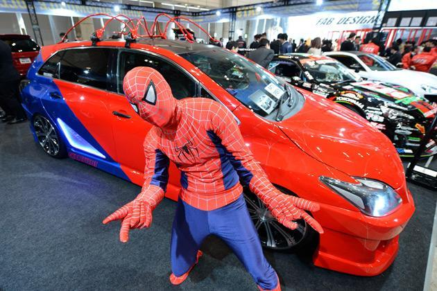 With a Spiderman-costume, a student poses in front of a Toyota Mark-X based vehicle, designed by NATS (Japan Automobile Collage) students, displayed during the Tokyo Auto Salon 2013 exhibition at the Makuhari Messe in Chiba on January 11, 2013. A total of 452 domestic and foreign companies participated in the three-day-long custom car exhibition with some 800 vehicles on display. AFP PHOTO / TOSHIFUMI KITAMURA