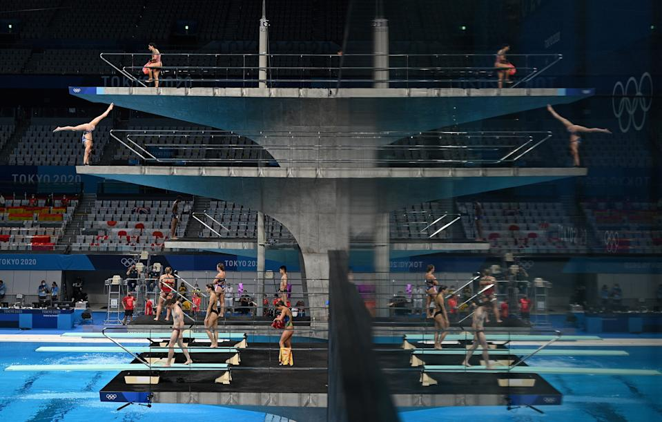 <p>A picture shows the reflection of the boards as divers warm up ahead of a diving session during the Tokyo 2020 Olympic Games at the Tokyo Aquatics Centre in Tokyo on July 27, 2021. (Photo by Oli SCARFF / AFP)</p>