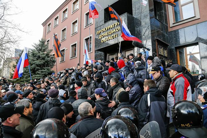 Pro-Russia demonstrators storm the prosecutor-general's office during a rally in Donetsk, Ukraine, Sunday, March 16, 2014. Pro-Russia demonstrators in the eastern city of Donetsk called Sunday for a referendum similar to the one in Crimea as some of them stormed the prosecutor-general's office. (AP Photo/Andrey Basevich)