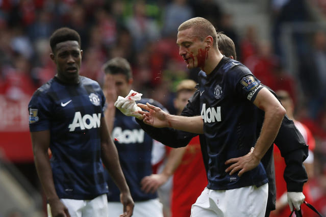 Manchester United's Nemanja Vidic, right, leaves the pitch after a nose bleed during their English Premier League soccer match against Southampton at St Mary's stadium, Southampton, England, Sunday, May 11, 2014. (AP Photo/Sang Tan)