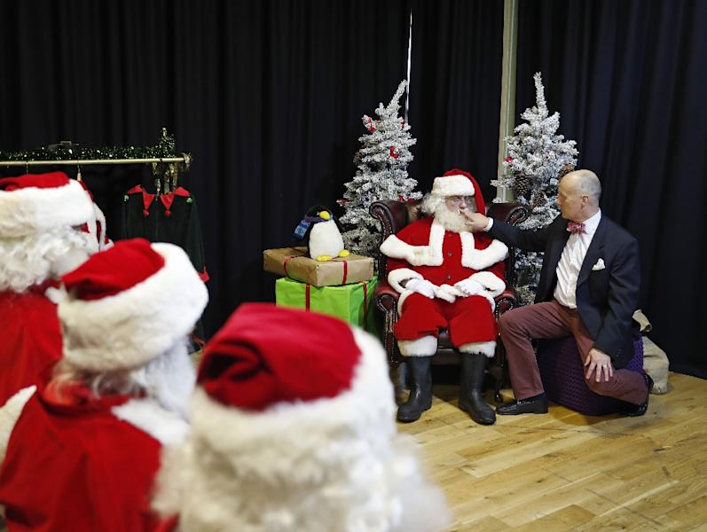 Instructor James Lovell adjusts the costume of a student Santa during a training session at The Ministry of Fun Santa School in London, on November 16, 2017 (AFP Photo/ADRIAN DENNIS)