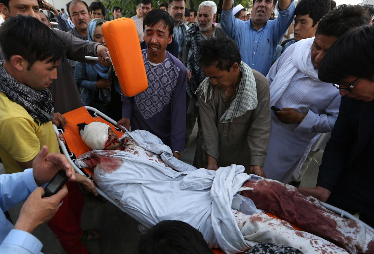 Afghans help a man injured in a deadly explosion that struck a protest march by ethnic Hazaras, in Kabul, Afghanistan, Saturday, July 23, 2016. Afghan Health Ministry officials say tens of people have been killed and over 200 wounded in the bombing Saturday, that was claimed by the Islamic State group according to a statement posted on the IS-linked Aamaq online news agency. The protesters Saturday were demanding that a major regional electric power line be routed through their impoverished home province. (AP Photo/Rahmat Gul)