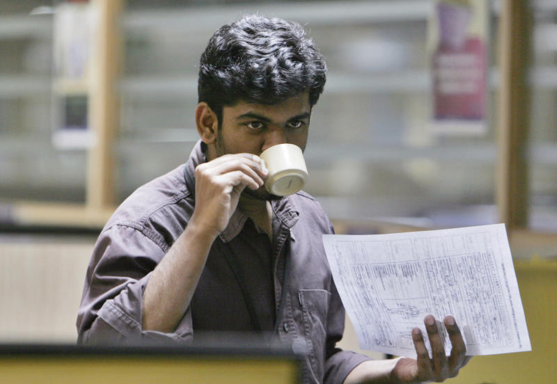 FILE - In this Nov. 18, 2008 file photo, an employee of HTMT Global Solutions drinks tea as he holds a document of an American client at the process center of Concetra, a U.S.-based insurance company, in Bangalore, India. Low cost efficiency put India's outsourcing companies at the heart of global business and created a multibillion dollar industry that for years has skated over criticism it was eliminating white collar jobs in rich nations. Now, the industry's long-held fears of a backlash are being realized in its crucial U.S. market. (AP Photo/Aijaz Rahi, File)