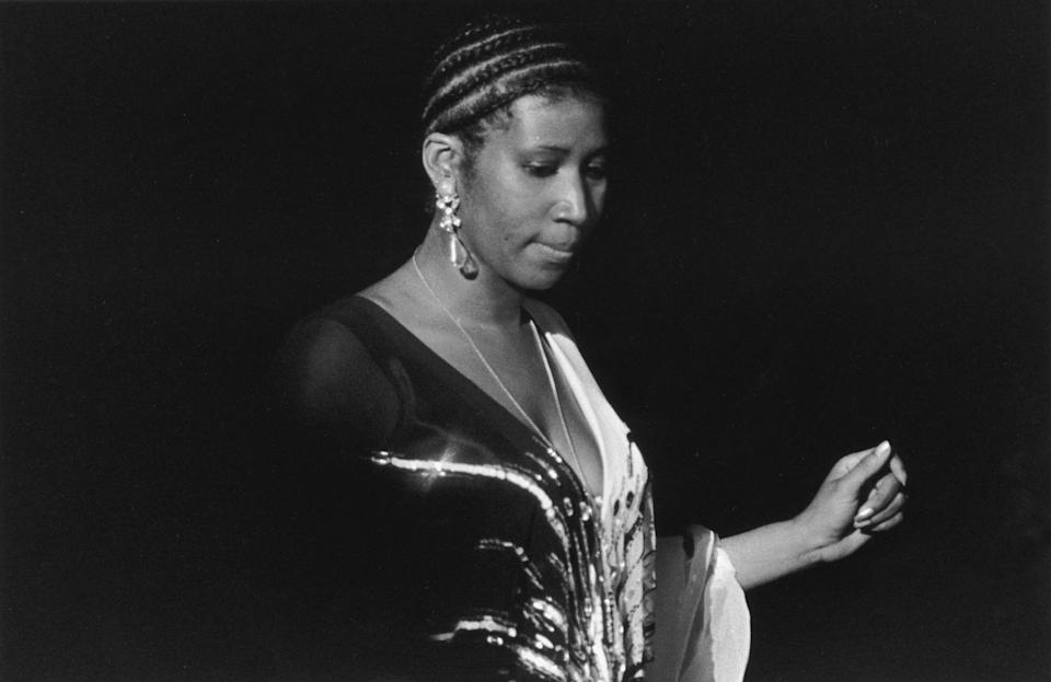 <p>Aretha Franklin snaps her fingers during a performance on stage at the Astrodome Jazz Festival in Houston, Tx. Franklin has tightly braided hair and wears a sequined chiffon gown with a plunging neckline. (Photo by Tad Hershorn/Hulton Archive/Getty Images) </p>