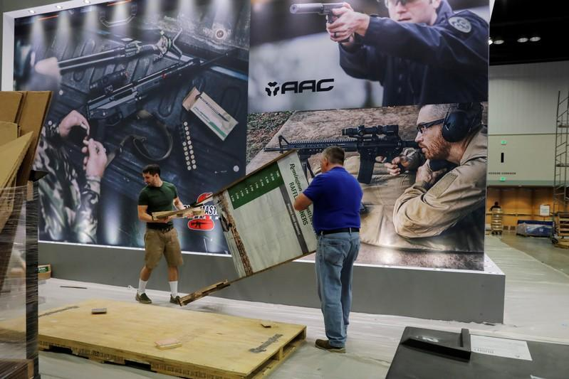 Workers prepare a display at the Remington booth inside of the Indiana Convention Center the day before the start of the annual National Rifle Association (NRA) convention in Indianapolis, Indiana