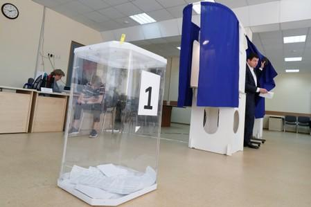 A man walks out of a voting booth at a polling station during the Moscow city parliament election in Moscow