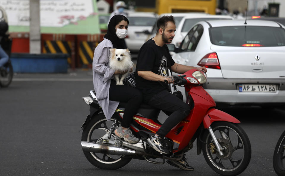 A woman holds a dog on a motorcycle while crossing an intersection in downtown Tehran, Iran, Tuesday, May 11, 2021. (AP Photo/Vahid Salemi)