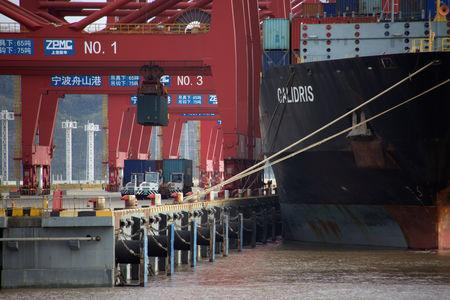 Trucks transport containers next to a container ship at a port in Zhoushan