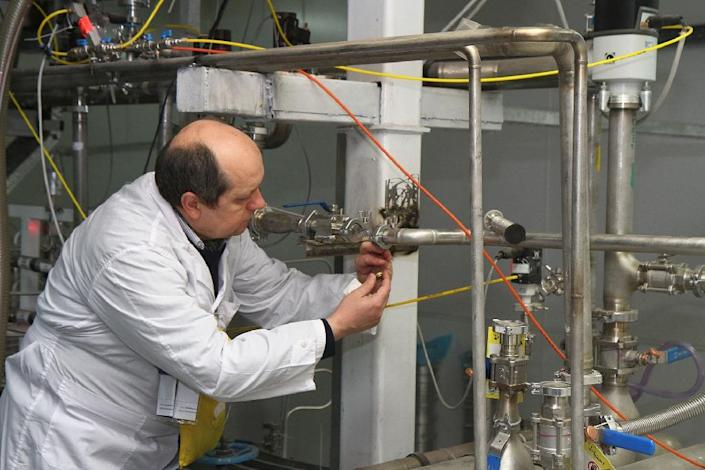 An International Atomic Energy Agency (IAEA) inspector disconnects the twin cascades for 20 percent uranium production at the nuclear power plant of Natanz on January, 20, 2014 (AFP Photo/Kazem Ghane)