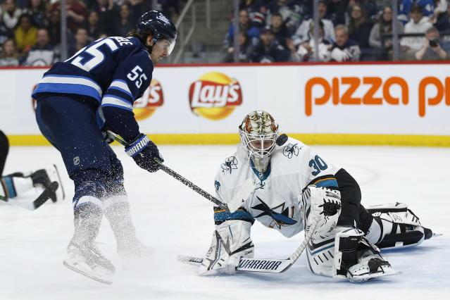 San Jose Sharks goaltender Aaron Dell (30) makes the save on a shot by Winnipeg Jets' Mark Scheifele (55) during the second period of an NHL hockey game Friday, Feb. 14, 2020, in Winnipeg, Manitoba. (John Woods/The Canadian Press via AP)