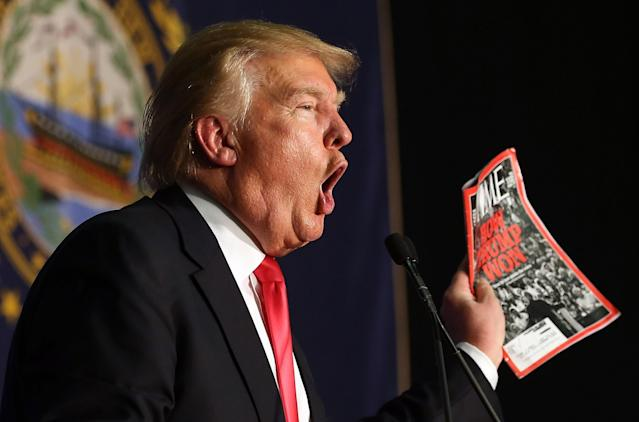 Donald Trump holds up a TIME magazine in Feb. 2016 at a rally in New Hampshire (Getty)