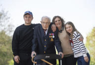 FILE - In this April 16, 2020 file photo, 99-year-old war veteran Captain Tom Moore, with from left, his grandson Benji, daughter Hannah Ingram-Moore and granddaughter Georgia, at his home in Marston Moretaine, England, after he achieved his goal of 100 laps of his garden. The legacy of Capt. Tom Moore, the super fundraiser who died Tuesday, Feb. 2, 2021 of COVID-19, lives on in Imogen Papworth-Heidel — and many others. The 11-year-old soccer player, who dreams of playing for England, watched Capt. Tom pushing his walker up and down his garden to raise money for the National Health Service. So she decided to help by doing something she's good at: keepy uppies — kicking the ball into the air and passing it from one foot to the other without letting it touch the ground. Imogen was able to raise 15,000 pounds ($20,500) for key workers. Similar fundraising feats have been performed by a 5-year-old amputee and a 90-year-old woman in the Scottish Highland. (Joe Giddens/PA via AP, File)
