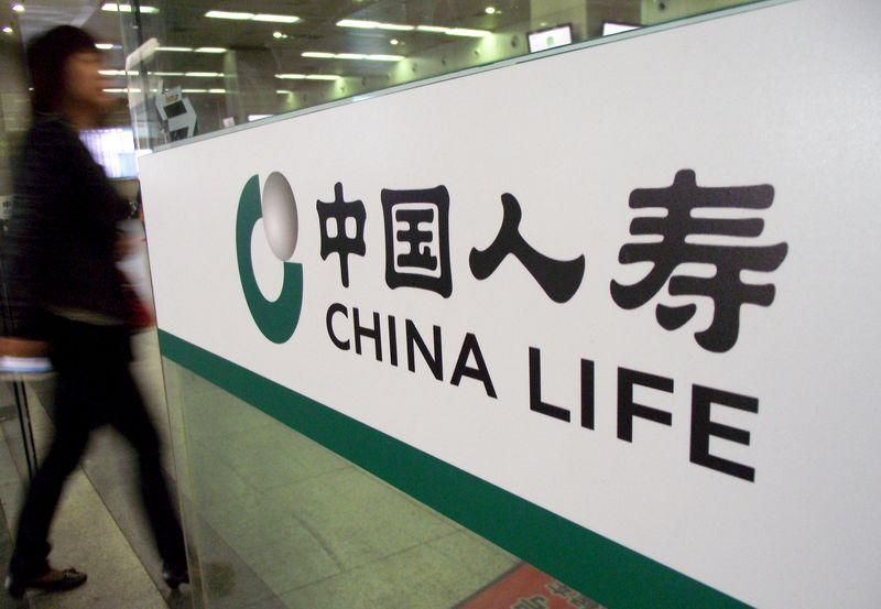 A woman walks past a door with a logo of China Life insurance, in Nanjing