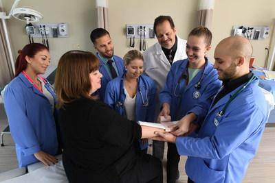 PA students led by Dr.  designate Payne (center back row)  accept hands-on  rehearse in classes and clinical rotations.