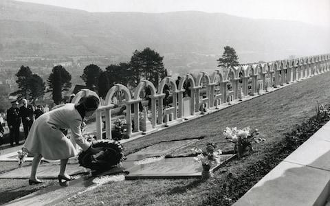 Queen Elizabeth II laying a wreath near the graves of the victims of the Aberfan disaster - Credit: PA