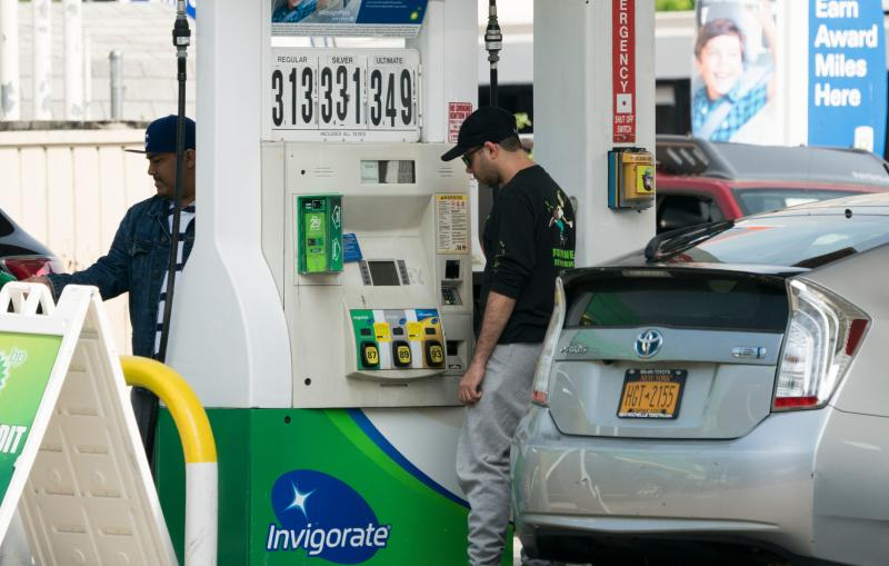 """Customers pump gasoline into their cars at a gas station in the Bronx, where gas prices have been raised to over $ 3.00 per gallon, June 1, 2018 in New York. - Rising gasoline prices in New York is having an effect on Uber and Lyft drivers revenues. This due to a rise on oil prices. (Photo by Don EMMERT / AFP) / TO GO WITH story by Ali BEKHTAOUI on """"Uber, Lyft drivers pinched by higher gasoline prices"""" (Photo credit should read DON EMMERT/AFP/Getty Images)"""