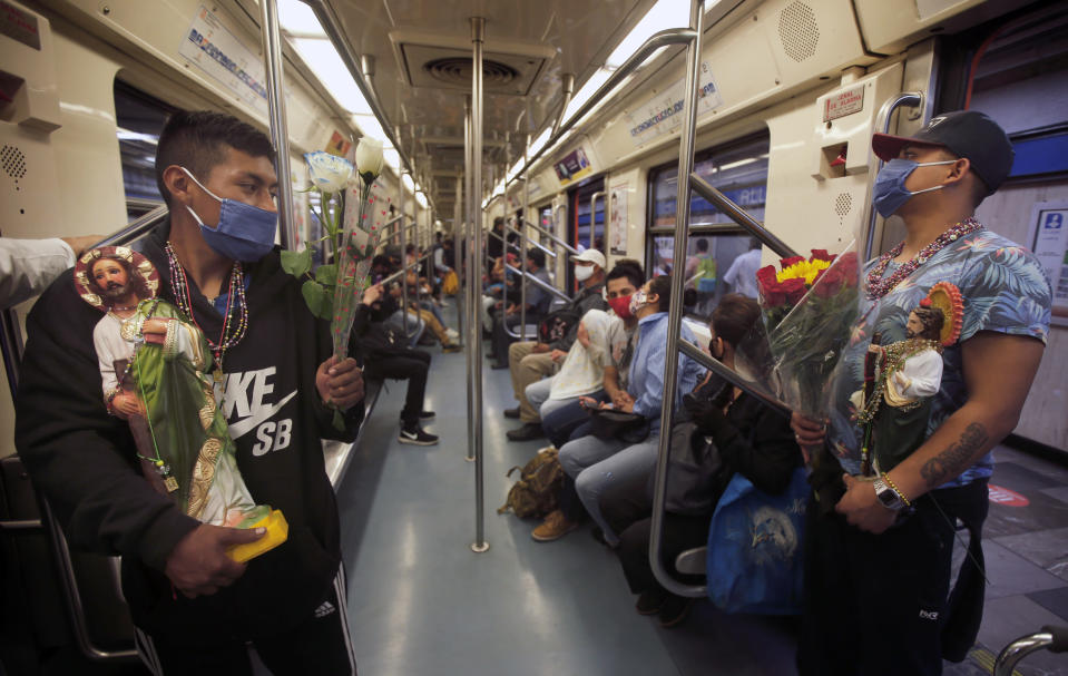 Devotees travel on the subway with their Saint Jude statues during the annual pilgrimage honoring Jude, the patron saint of lost causes, in Mexico City, Wednesday, Oct. 28, 2020. Thousands of Mexicans did not miss this year to mark St. Jude's feast day, but the pandemic caused Masses to be canceled and the rivers of people of other years outside the San Hipolito Catholic church were replaced by orderly lines of masked worshipers waiting their turn for a blessing. (AP Photo/Marco Ugarte)