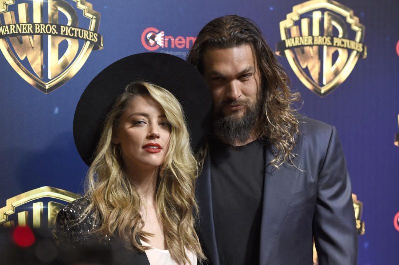 "Amber Heard, left, and Jason Momoa, cast members in the upcoming film ""Aquaman,"" arrive at the Warner Bros. presentation at CinemaCon 2018, the official convention of the National Association of Theatre Owners, at Caesars Palace on Tuesday, April 24, 2018, in Las Vegas. (Photo by Chris Pizzello/Invision/AP)"