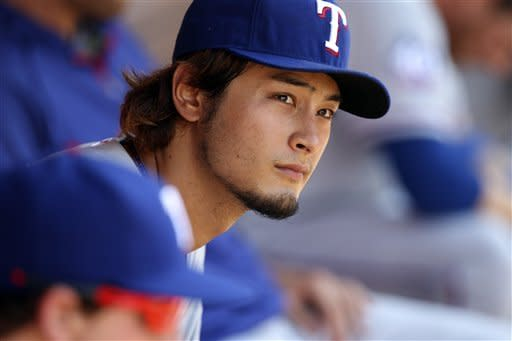 Texas Rangers starting pitcher Yu Darvish, of Japan, sits in the dugout during between innings of a baseball game against the Los Angeles Angels in Anaheim, Calif., Saturday, July 21, 2012. (AP Photo/Reed Saxon)