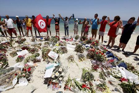 FILE PHOTO: People join hands as they observe a minute's silence in memory of those killed in an attack by an Islamist gunman, at a beach in Sousse, Tunisia July 3, 2015. REUTERS/Anis Mili/File Photo