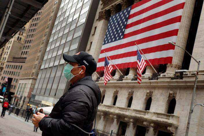 A man wears a mask to prevent exposure to the coronavirus disease (COVID-19) while walking past the New York Stock Exchange in New York, March 17, 2020.