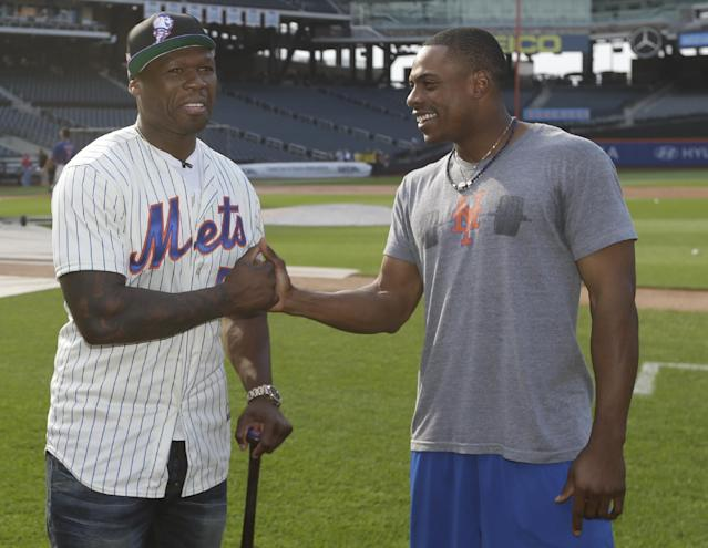 Rapper 50 Cent talks with New York Mets' Curtis Granderson, right, before the Mets' baseball game against the Pittsburgh Pirates Tuesday, May 27, 2014, in New York. (AP Photo/Frank Franklin)