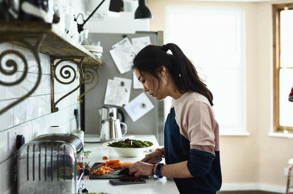Side view portrait of attractive Asian woman in her 30s, cutting carrots on chopping board, concentrating and using knife