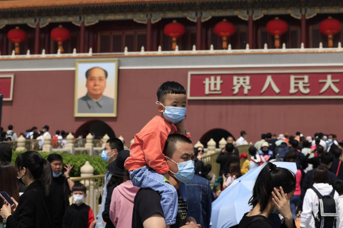 A man and child wearing masks visit Tiananmen Gate near the portrait of Mao Zedong in Beijing on May 3, 2021. China's population growth is falling closer to zero as fewer couples have children, the government announced Tuesday, May 11, 2021, adding to strains on an aging society with a shrinking workforce. (AP Photo/Ng Han Guan)