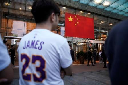 Man wearing a T-shirt with name and number of LeBron James of NBA Los Angeles Lakers stands outside a Ritz-Carlton hotel in Shanghai,