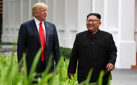 US President Donald Trump and North Korea leader Kim Jong Un walk from their lunch at the Capella resort on Sentosa Island Tuesday - Credit: Evan Vucci/AP