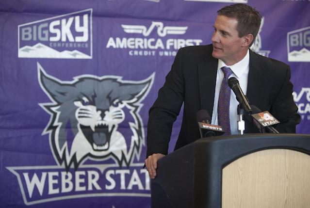 Jay Hill speaks with reporters at a press conference where he was introduced as the new head NCAA college football coach at Weber State University, Thursday, Dec. 12, 2013 in Ogden, Utah. (AP Photo/Standard-Examiner, Benjamin Zack)