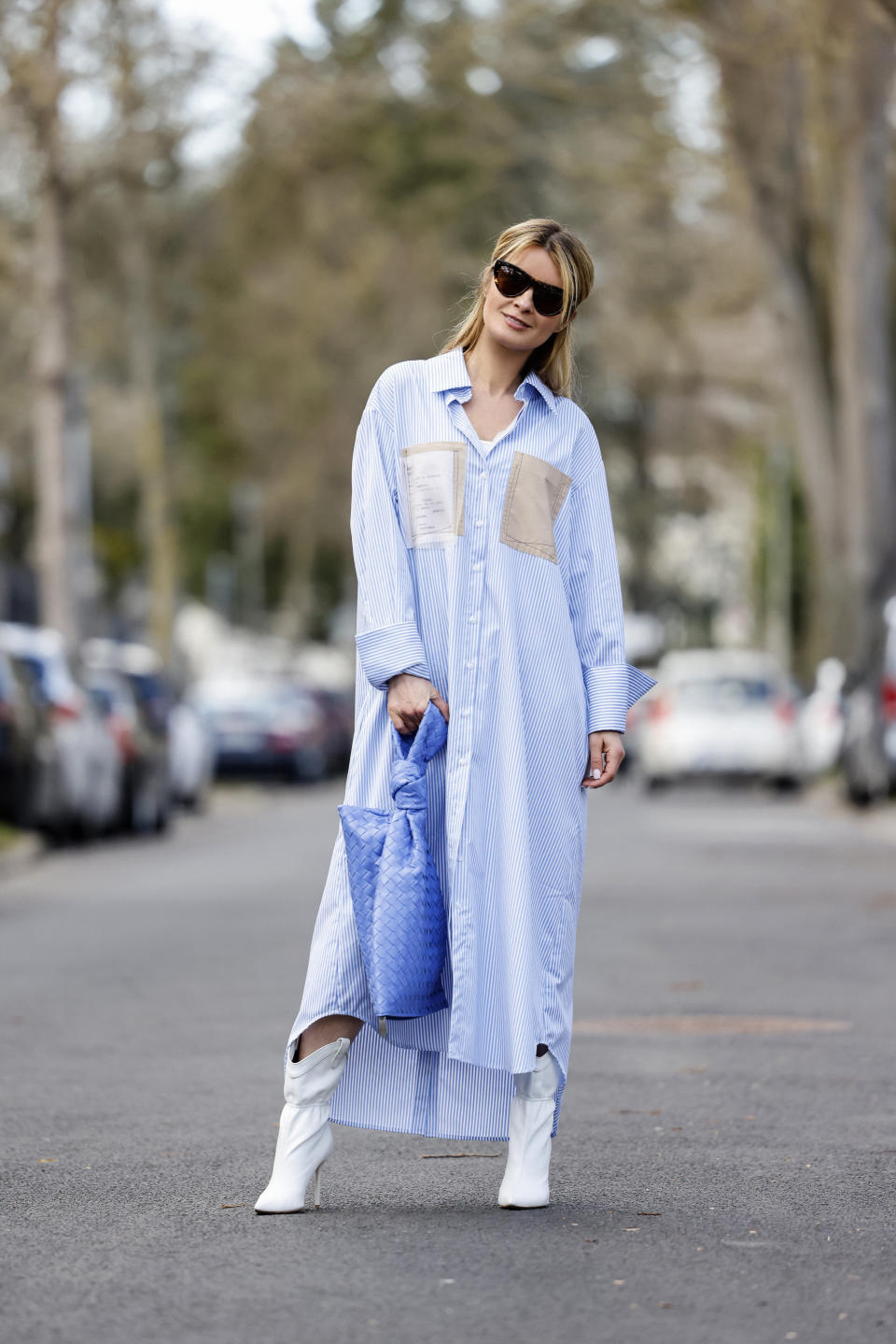 DUSSELDORF, GERMANY - MARCH 18: Influencer Gitta Banko wearing white high heel ankle booties by Malone Souliers, a light blue and white striped long blouse dress by Balossa, a blue bag by Bottega Veneta and sunglasses by Bottega Veneta during a street style shooting on March 18, 2021 in Dusseldorf, Germany. (Photo by Streetstyleshooters/Getty Images)