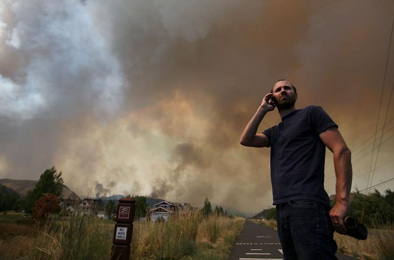 Kevin Bullock, of Bellevue, Idaho, watches smoke from the 64,000 acre Beaver Creek Fire on Friday, Aug., 16, 2013 north of Hailey, Idaho. A number of residential neighborhoods have been evacuated because of the blaze.(AP Photo/Times-News, Ashley Smith) MANDATORY CREDIT