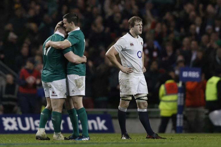 Ireland's Cian Healy (L) and fly-half Johnny Sexton embrace as England's lock Joe Launchbury (R) reacts at the final whistle in the Six Nations international rugby union match March 18, 2017