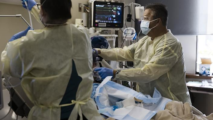 Healthcare workers treat a patient inside a negative pressure room in the Covid-19 intensive care unit (ICU) at Freeman Hospital West in Joplin, Missouri, U.S., on Tuesday, Aug. 3, 2021. (Angus Mordant/Bloomberg via Getty Images)