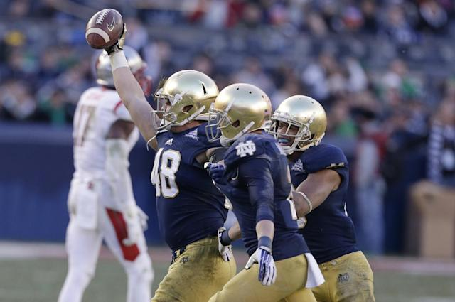 Notre Dame's Dan Fox (48) celebrates an interception with teammates during the second half against Rutgers in the Pinstripe Bowl NCAA college football game Saturday, Dec. 28, 2013, at Yankee Stadium in New York. Notre Dame won the game 29-16. (AP Photo/Frank Franklin II)