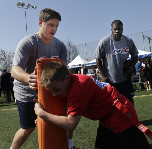 NFL draft prospects Luke Joeckel of Texas A&M, left, and Menelik Watson of Florida State participate in a youth football clinic in New York,Wednesday, April 24, 2013. (AP Photo/Seth Wenig)