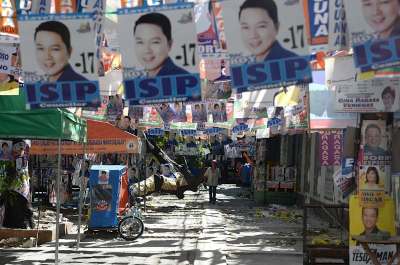 Election posters hang over a street in Manila on May 8, 2016, on the eve of the presidential election (AFP Photo/Ted Aljibe)