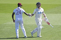 West Indies Kermit Roach, left, shakes hands with New Zealand's Kane Williamson at the close of the New Zealand innings during play on day two of the first cricket test between the West Indies and New Zealand in Hamilton, New Zealand, Friday, Dec. 4, 2020. (Andrew Cornaga/Photosport via AP)