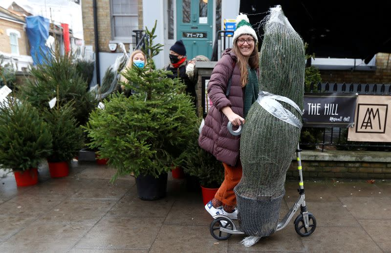 FILE PHOTO: A woman who rented a Christmas tree from Christmas on The Hill carries her tree away on a scooter, in London